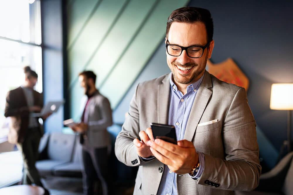 Geschäftsmann, der E-Mails am Telefon im modernen Büro überprüft